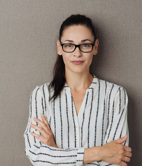 Pert young woman wearing glasses standing with crossed arms staring at the camera over a grey brown studio background with copy space